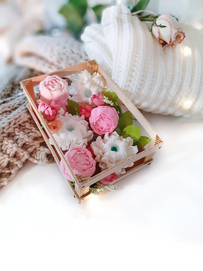 在箱子、被编织的衣物、玫瑰和光的肥皂floweres在白色背景 图库摄影
