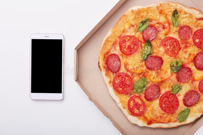 在箱子和智能手机的比萨有在白色桌,可口意大利辣味香肠顶视图上的黑屏的在轻的背景的 库存图片