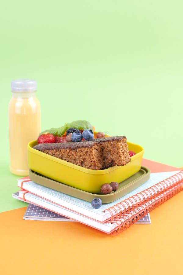 在箱子和汁液的学校午餐用在绿色背景和书的果子 文本的空位 复制空间 免版税图库摄影