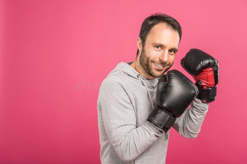 在箱子手套的微笑的男性拳击手训练,被隔绝 免版税库存照片