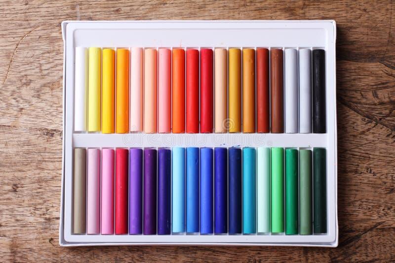 在箱子的五颜六色的白垩柔和的淡色彩在木背景 免版税库存照片