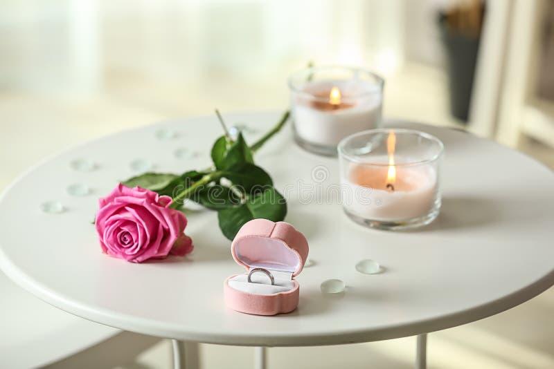 在箱子的定婚戒指有在白色桌上的玫瑰色和燃烧的蜡烛的 图库摄影