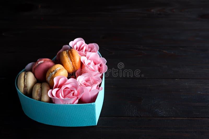 在箱子的蛋白杏仁饼干 欢乐回合蓝色框用曲奇饼和罗斯黑暗的木背景的,拷贝空间 免版税图库摄影