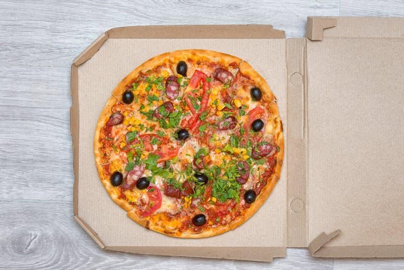 在箱子的鲜美意大利薄饼在一张木桌上 薄饼发运 顶视图 复制空间 免版税库存图片