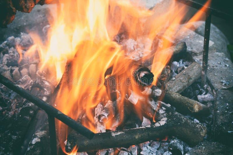 在篝火的灼烧的木柴 烧在与烟的格栅的火焰 放火或自然灾害 火和火焰纹理, dar 免版税库存照片