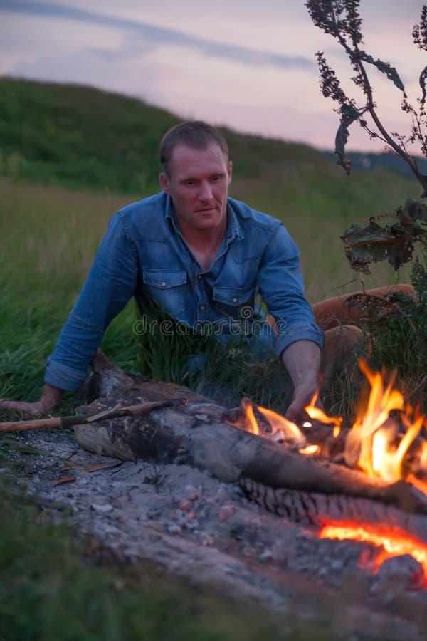 在篝火附近的人在日落期间 图库摄影