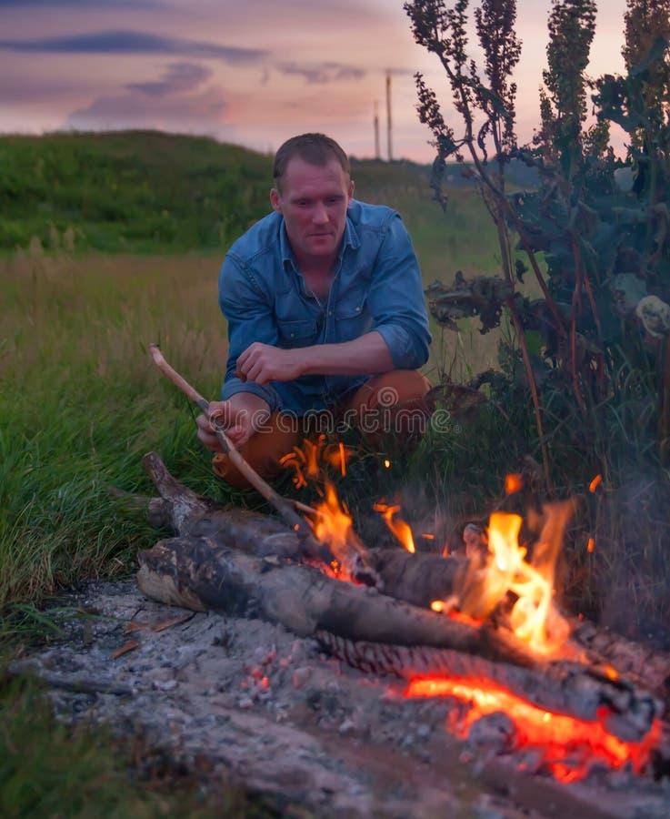在篝火附近的人本质上 免版税图库摄影