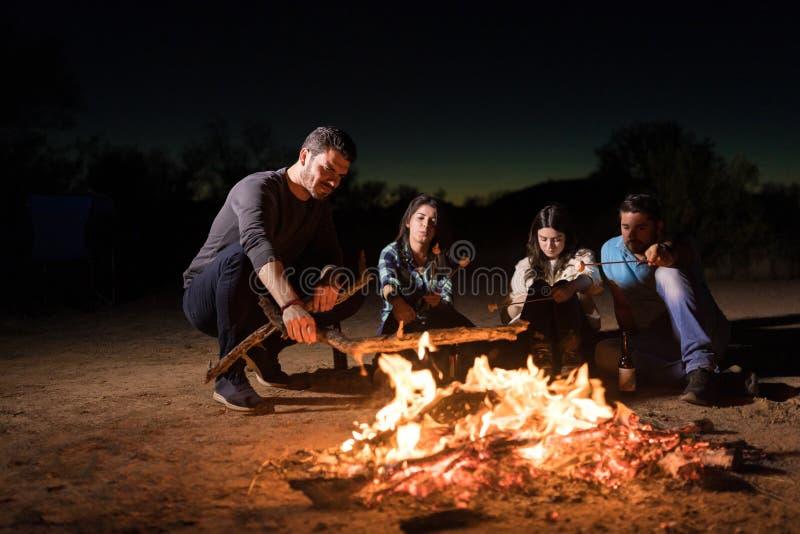 在篝火附近的伙计,当野营时 免版税图库摄影
