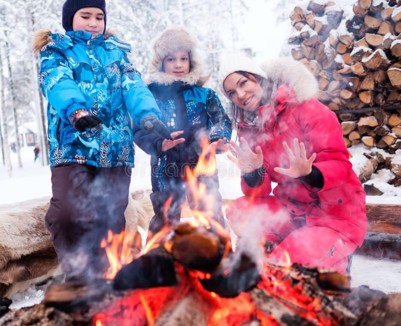 在篝火附近的家庭在冬天风景 免版税库存图片