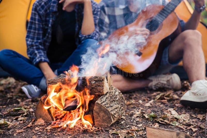在篝火附近结合坐与吉他在森林里 免版税库存图片