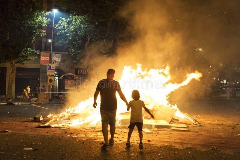 在篝火,巴塞罗那的父亲和儿子投掷的对象 免版税库存照片