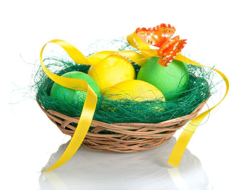 在篮子、蝴蝶和丝带的色的复活节彩蛋在白色 库存照片