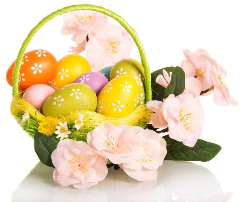 在篮子和分支的五颜六色的复活节彩蛋与被隔绝的花 免版税图库摄影