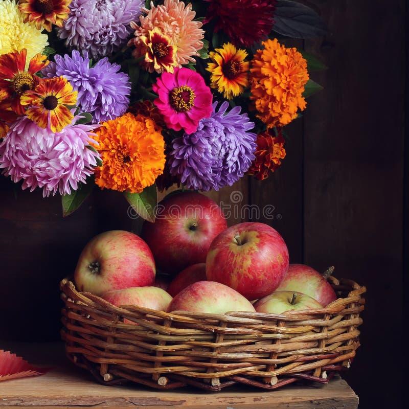 在篮子和秋天花束的成熟红色苹果 免版税图库摄影