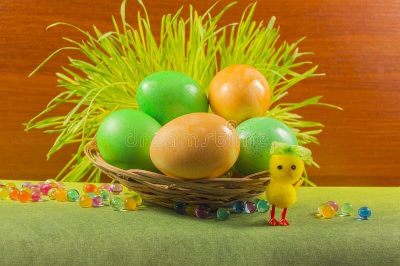 在篮子和鸡的五颜六色的复活节彩蛋 免版税库存图片