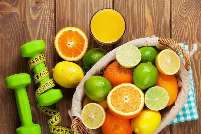 在篮子和dumbells的柑橘水果 桔子、石灰和柠檬 免版税库存图片