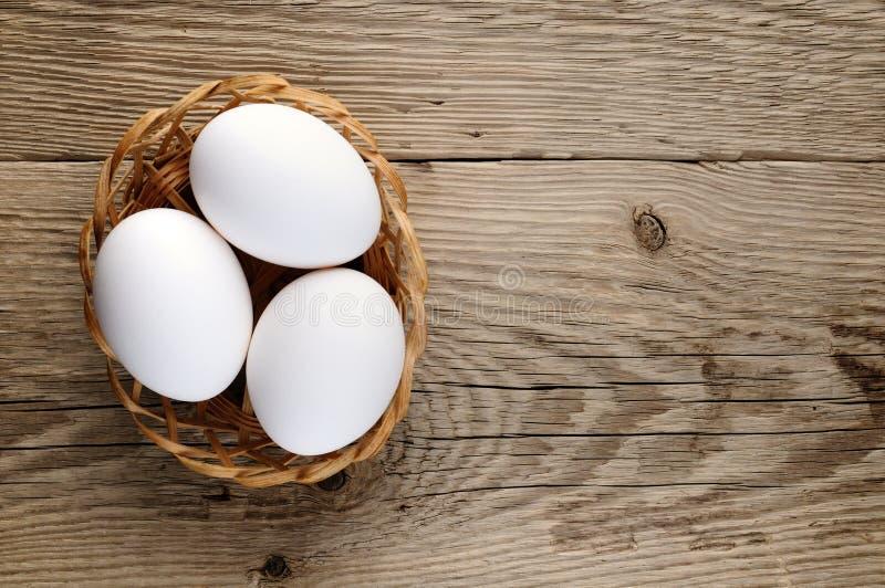 在篮子的三个白鸡蛋 免版税库存照片
