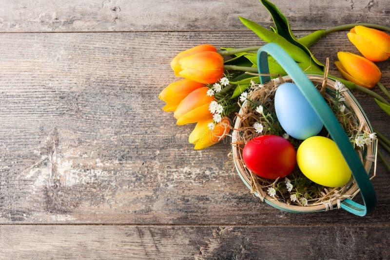 在篮子的五颜六色的在木桌上的复活节彩蛋和郁金香 库存照片