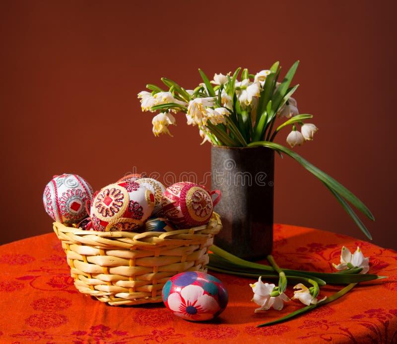 在篮子和snowdrops的五颜六色的复活节彩蛋 库存照片