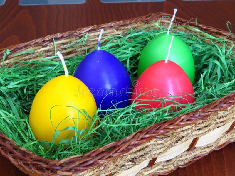 在篮子的五颜六色的蛋形蜡烛 复活节家装饰 免版税库存图片