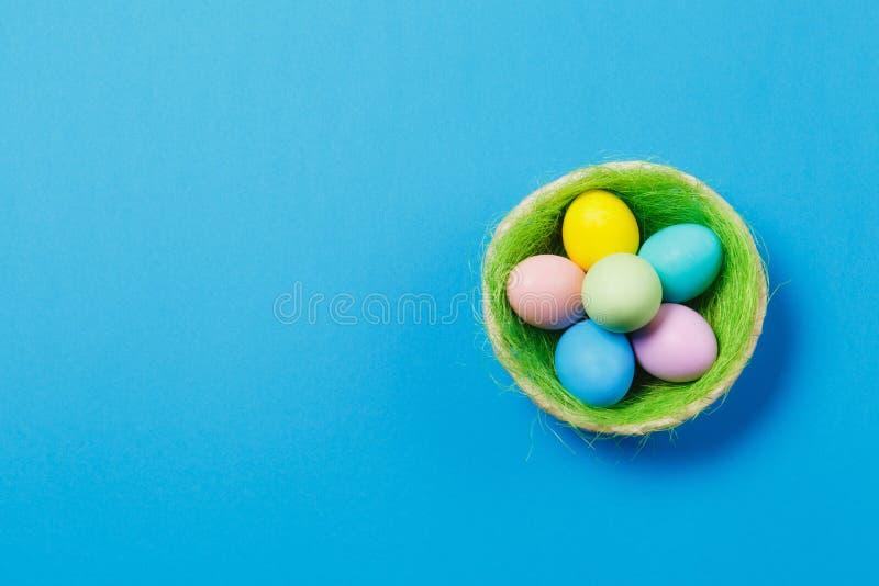 在篮子的六个五颜六色的淡色单音被绘的复活节彩蛋与在蓝色背景隔绝的绿草 愉快的复活节 库存图片