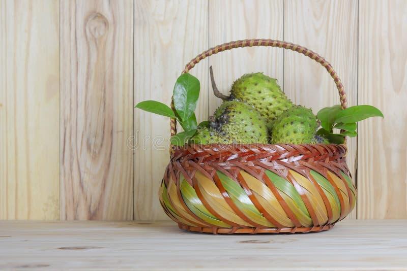 在篮子的刺番荔枝或多刺的南美番荔枝或番荔枝科在木桌上的muricata L 库存图片