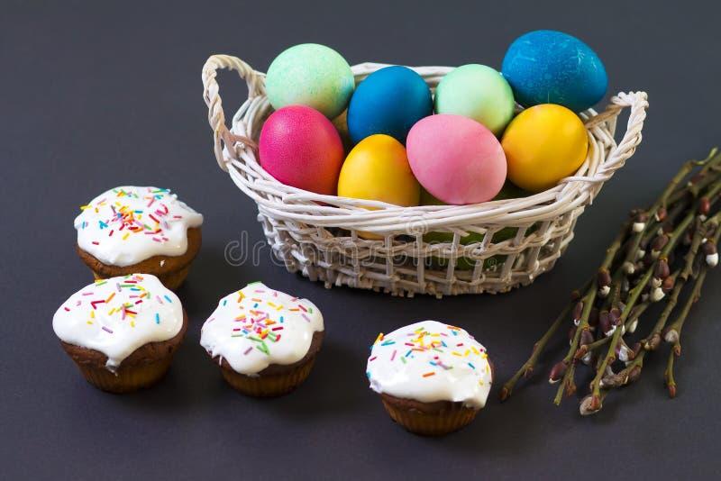 在篮子的复活节多彩多姿的鸡蛋和在黑背景的甜杯形蛋糕松饼 复活节概念性背景 免版税库存图片