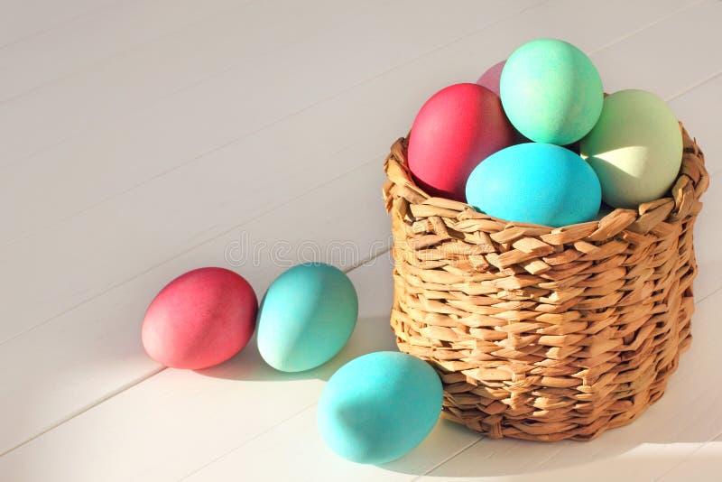 在篮子的复活节彩蛋在木背景 免版税库存图片