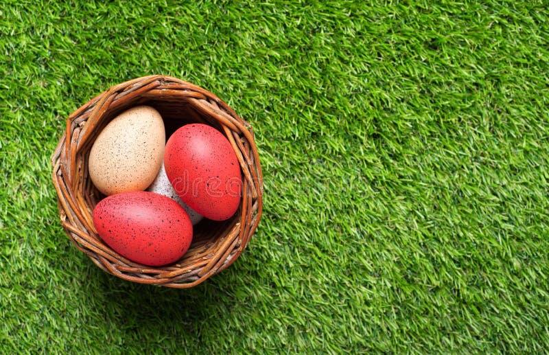 在篮子的复活节彩蛋在草 免版税图库摄影
