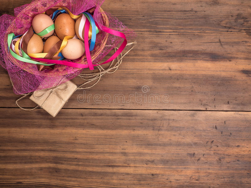 在篮子的复活节彩蛋与在木桌背景的色的丝带从老委员会的有礼物盒的 图库摄影