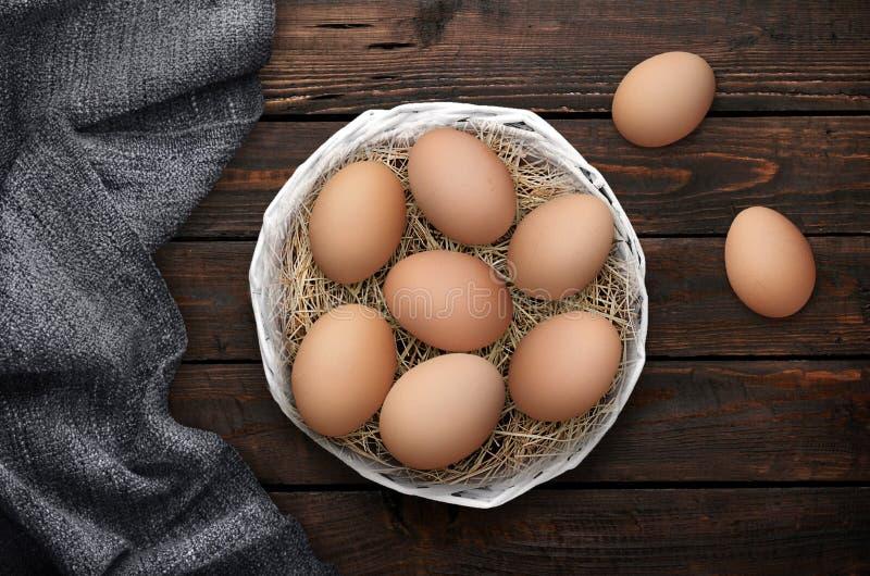 在篮子的复活节彩蛋在与布的木背景 免版税库存照片