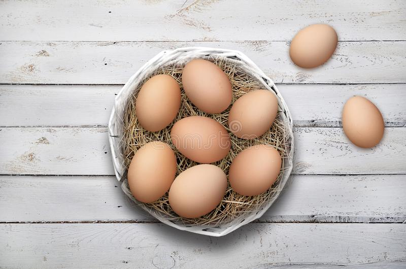 在篮子的复活节彩蛋在白色木背景 库存图片