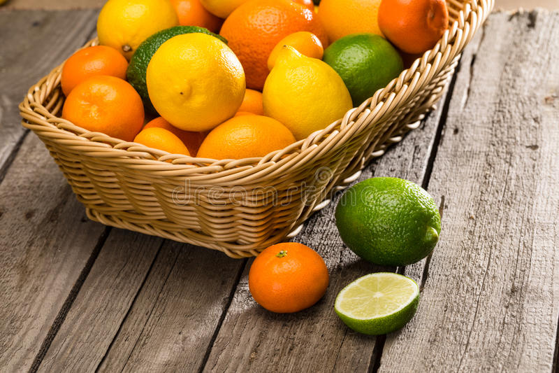 在篮子的新鲜的成熟柑橘水果在木桌上 库存照片