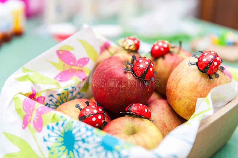 在篮子的新鲜的苹果与巧克力瓢虫 库存图片