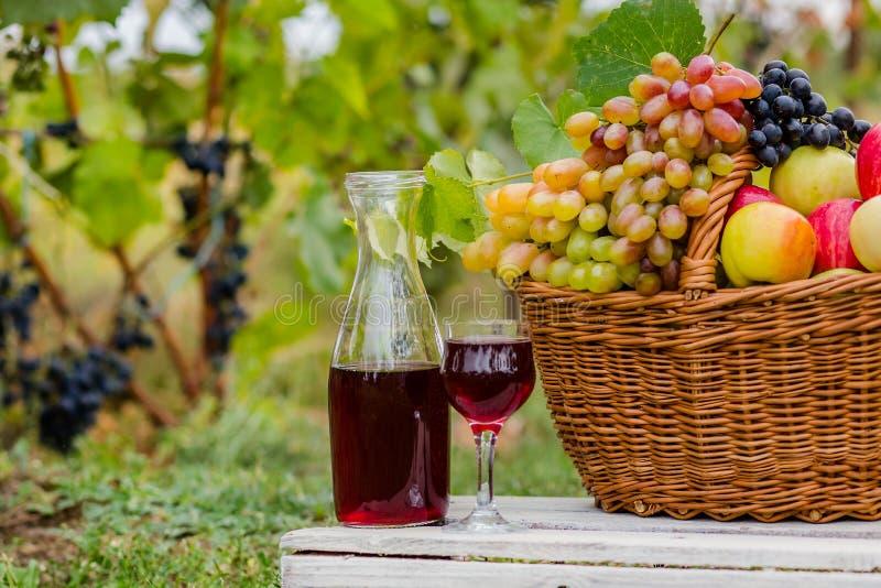 在篮子的有机果子在夏天草 蒸馏瓶和杯酒 库存照片