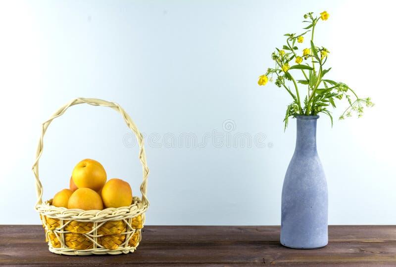 在篮子的杏子 有野花的花瓶在蓝色背景 夏天心情 免版税库存照片