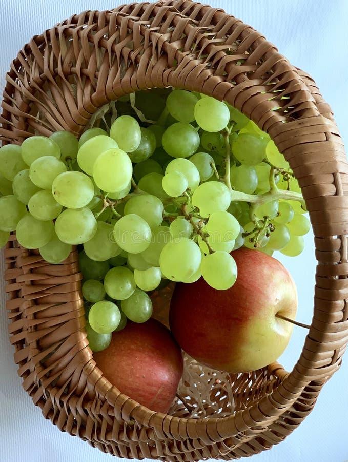 在篮子的美丽的夏天果子 黄色红色苹果和白葡萄 免版税库存图片