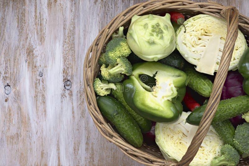 在篮子的菜在白色绘了木背景:黄瓜,硬花甘蓝,胡椒,圆白菜,撇蓝 免版税图库摄影
