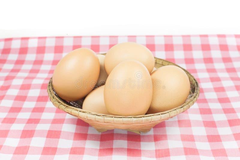 在篮子的鸡蛋在白色背景的桃红色颜色格子花呢披肩 免版税库存照片