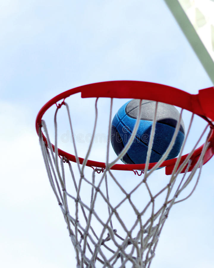 在篮球目标箍外缘的蓝色和黑篮球  库存照片