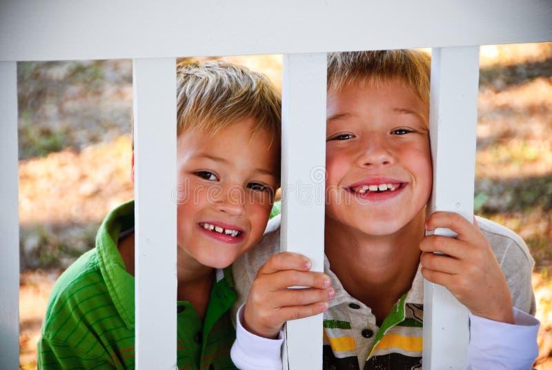 在篱芭后的两个逗人喜爱的小男孩 免版税库存图片