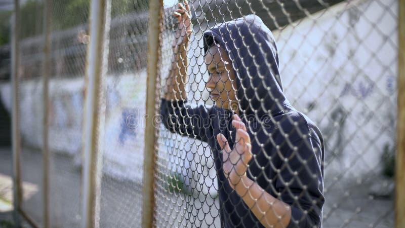 在篱芭后的移民少年作梦关于前途和安全,难民的 免版税库存图片