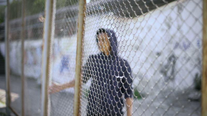 在篱芭后的美国黑人的男孩,流浪儿从家庭分离了,被扣留 库存图片