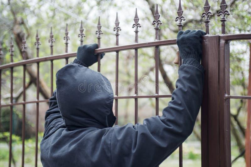 在篱芭特写镜头的手套的手 男性窃贼用在设法的手套的手爬上金属篱芭 图库摄影