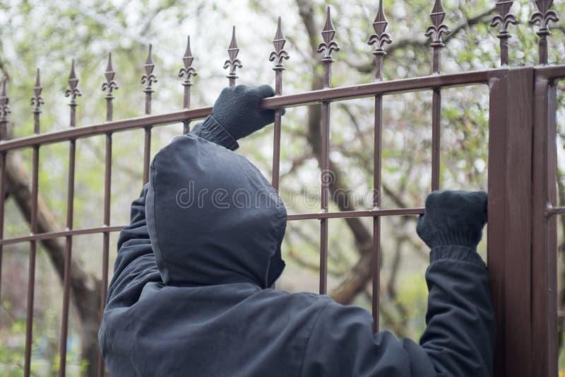 在篱芭特写镜头的手套的手 男性窃贼用在设法的手套的手爬上金属篱芭 库存图片