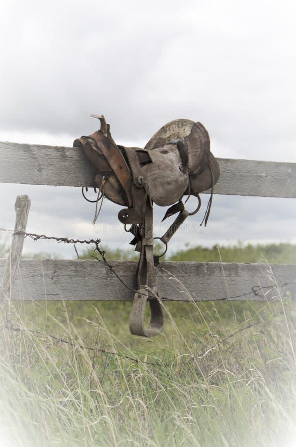 在篱芭的古色古香的西部古板的马鞍在牧场地 免版税图库摄影