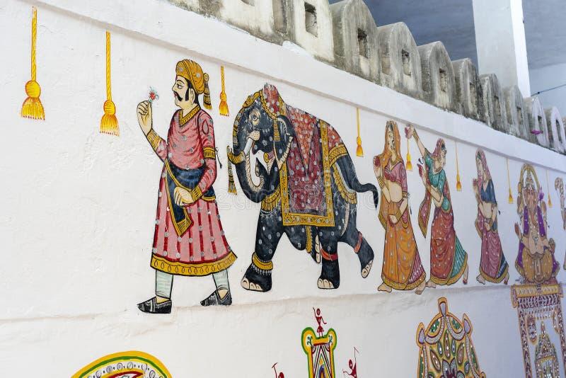 在篱芭的墙壁上的装饰传统图画在城市乌代浦,拉贾斯坦,印度的街道的 图库摄影