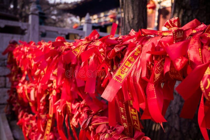 在篱芭的朱红色的丝带在佛教寺庙 免版税库存照片