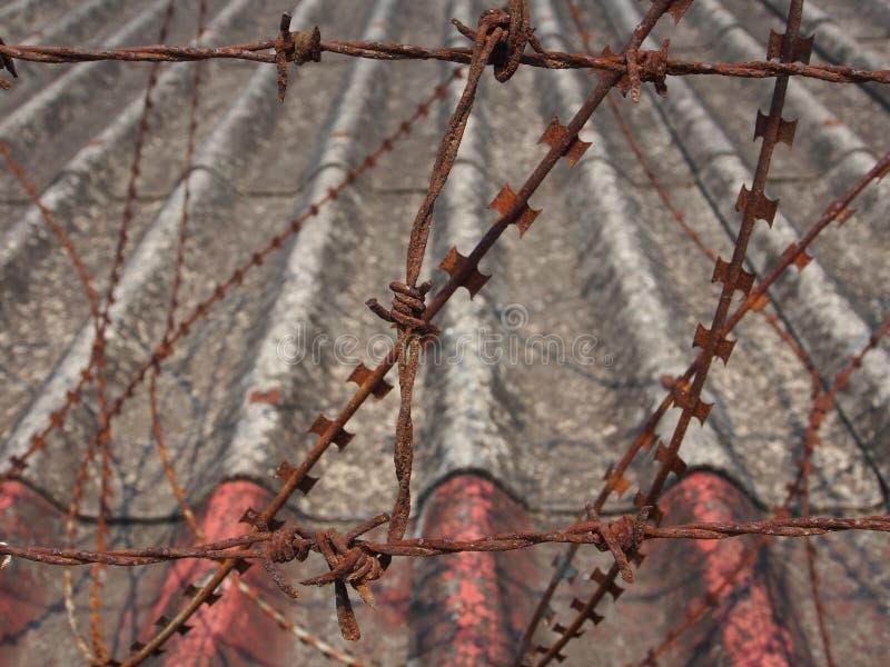 在篱芭的生锈的铁丝网有屋顶背景 库存照片