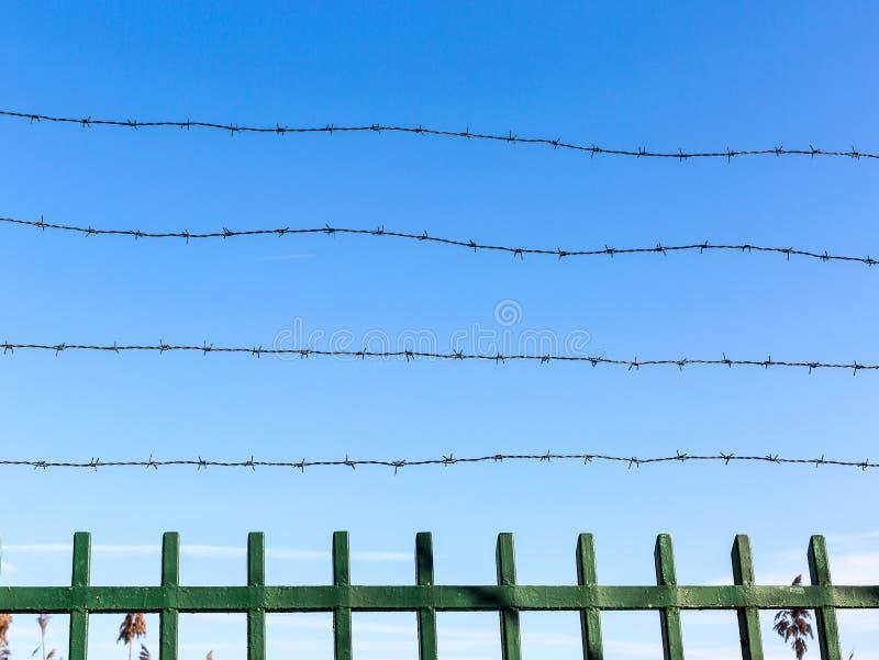 在篱芭的铁丝网反对天空蔚蓝 unfreedom和剥夺的标志 Unfreedom概念 免版税库存照片